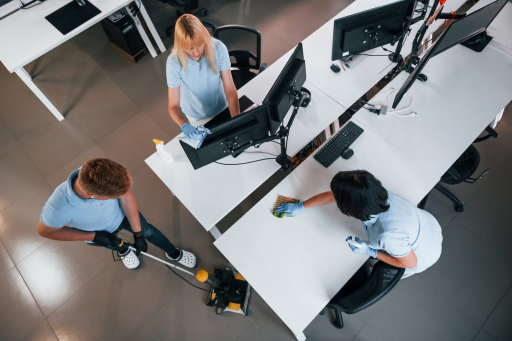 Top view. Group of workers clean modern office together at daytime